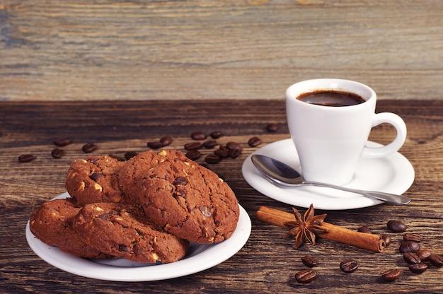 Prato com biscoitos de chocolate e xícara de café quente na mesa