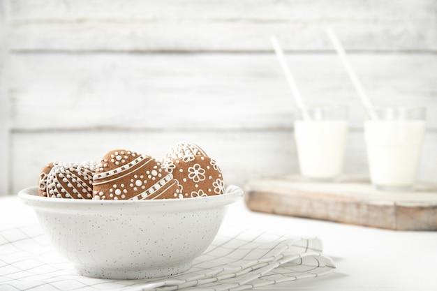 Prato com biscoitos de páscoa e um copo de leite. páscoa. biscoitos de páscoa lugar para texto.