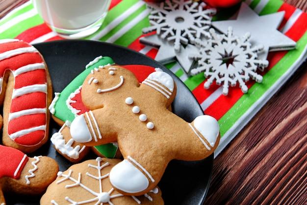 Prato com biscoitos saborosos e decoração de natal na mesa de madeira, vista de perto