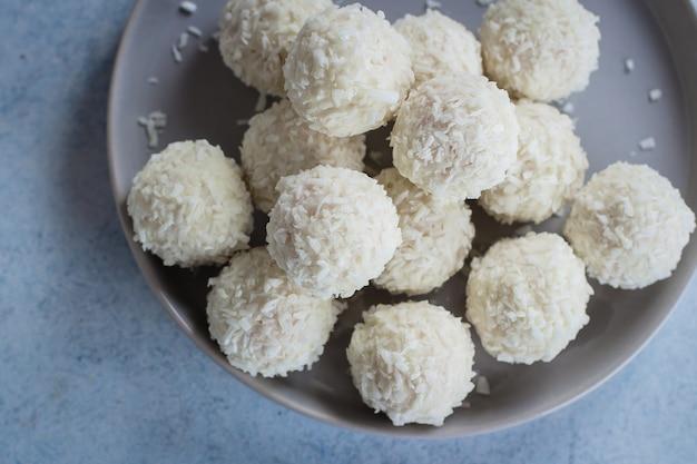 Prato com bombons de coco na mesa de madeira