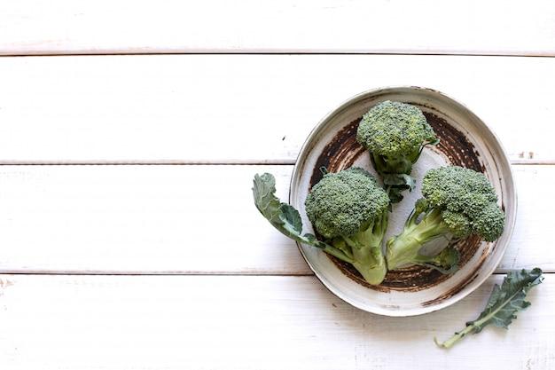 Prato com brócolis verde fresco, tiro de cima em uma textura rústica de madeira branca