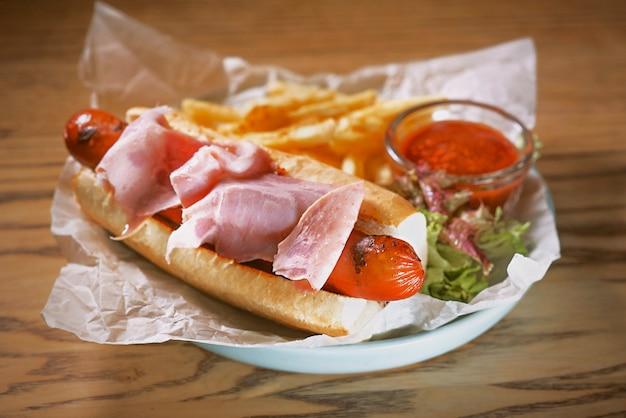 Prato com cachorro-quente com linguiça e presunto molho de tomate e catchup frito na mesa