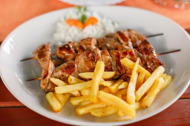 Prato com carne de porco shish kebab e batatas fritas
