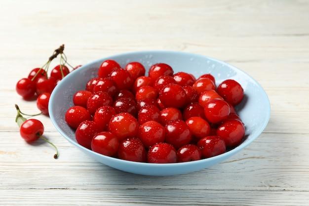 Prato com cereja vermelha em fundo branco de madeira