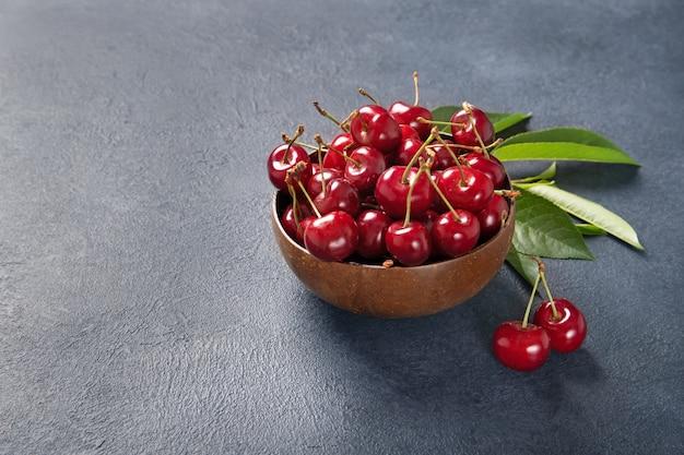 Prato com cerejas frescas com folhas verdes. fundo preto. lugar para texto