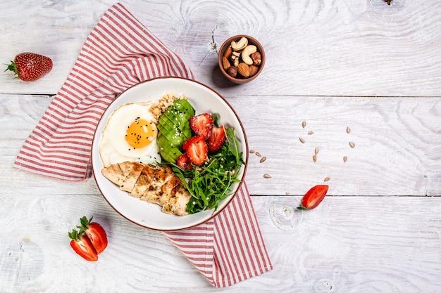 Prato com comida de dieta ceto, salada de frango com rúcula e morangos. vista do topo