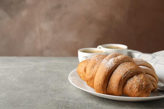 Prato com croissants, xícaras de café e toalha na mesa cinza, espaço para texto