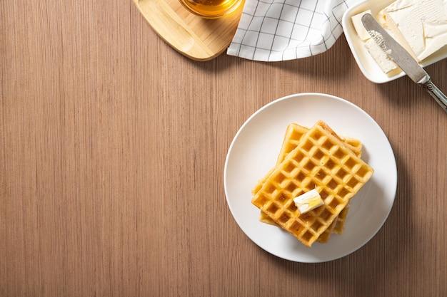 Prato com deliciosos waffles com mel e uma fatia de manteiga. lugar para texto