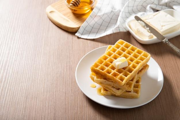 Prato com deliciosos waffles com mel e uma fatia de manteiga