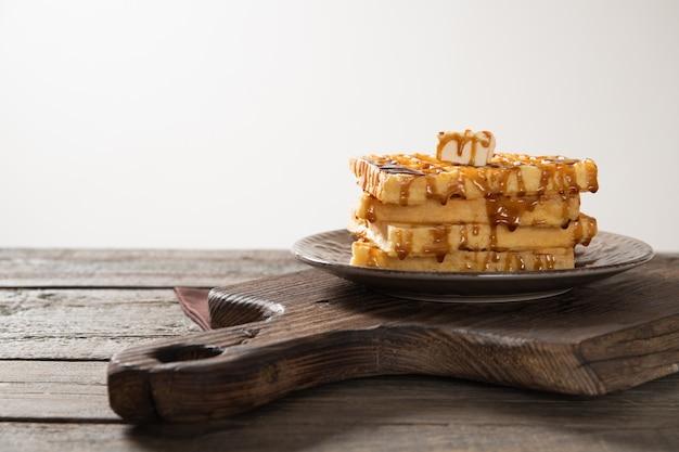 Prato com deliciosos waffles derramados com cobertura de caramelo e uma fatia de manteiga. sobre um fundo de madeira