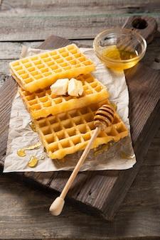 Prato com deliciosos waffles, mel e uma fatia de manteiga. sobre um fundo de madeira