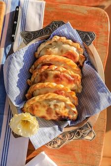 Prato com empanadas na mesa com decoração rústica e crioula
