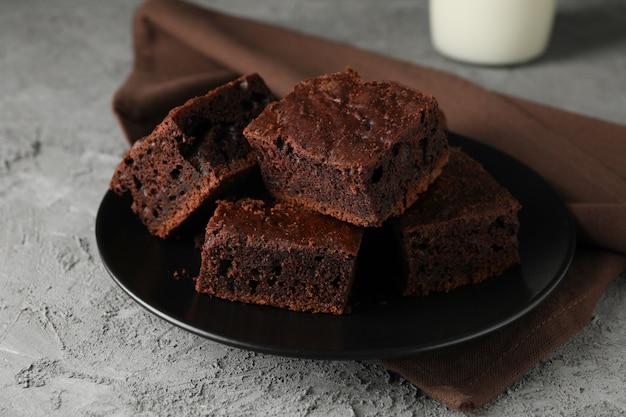 Prato com fatias de bolo de chocolate e garrafa de leite na mesa cinza, close-up
