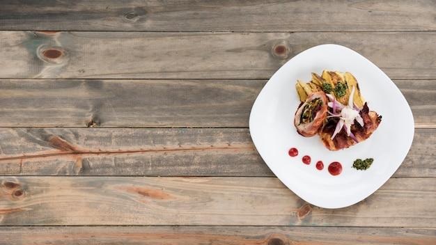 Prato com fatias de frango e batata rolo na mesa de madeira
