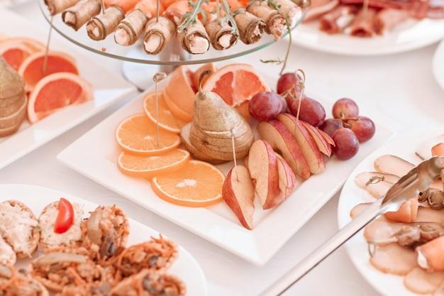 Prato com fatias de frutas diversas na mesa festiva