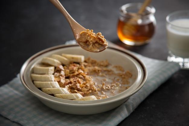 Prato com flocos de aveia integral com frutos de banana, mão humana com colher