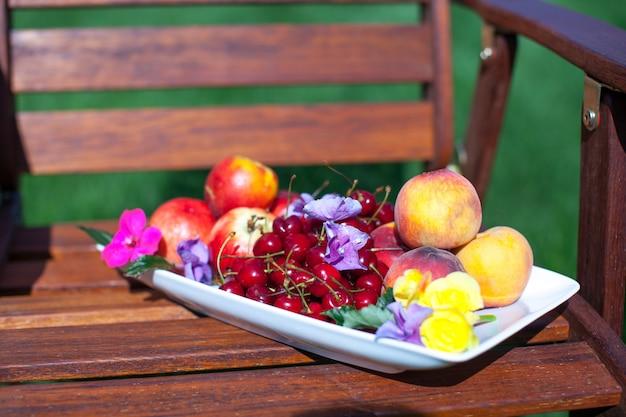 Prato com frutas frescas e flores em cadeiras de madeira