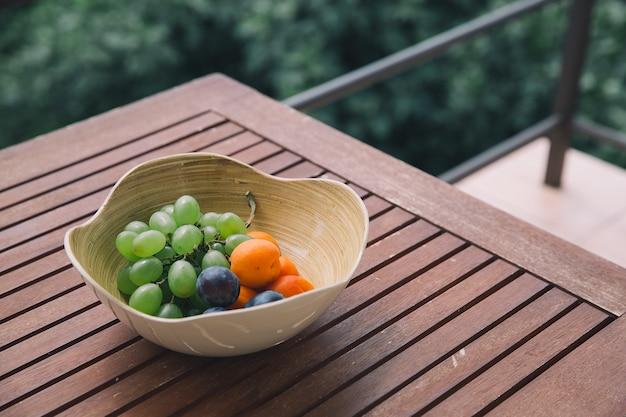Prato com frutas frescas misturadas no fundo da natureza. variedade de frutas suculentas na mesa de madeira