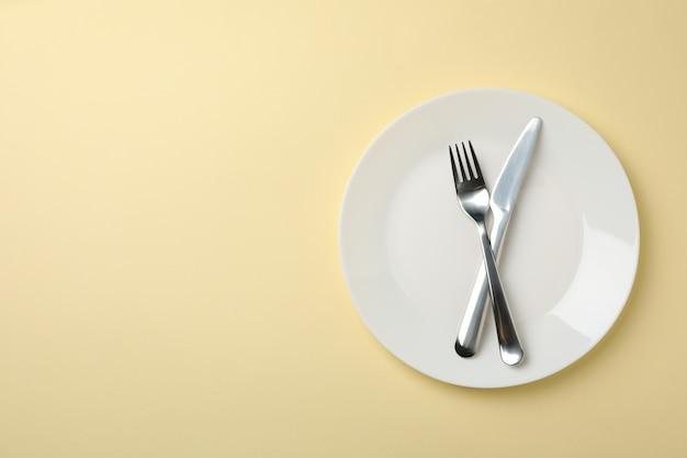 Prato com garfo e faca em bege, vista superior