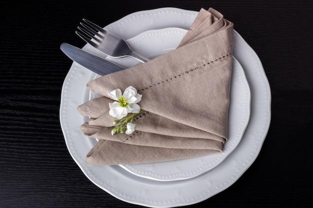 Prato com garfo, faca e guardanapo na mesa de madeira