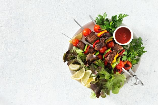 Prato com kebab de carne grelhada com legumes e molho na vista superior de mesa branca