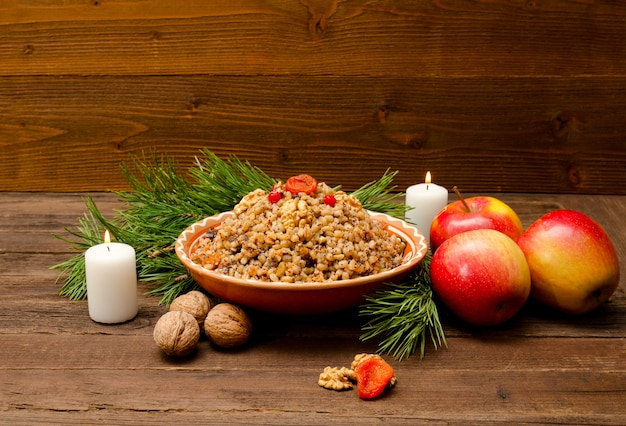 Prato com kutia - tradicional guloseima de natal dos eslavos na véspera de natal. galho de árvore de peles, maçã, vela em um fundo de madeira.