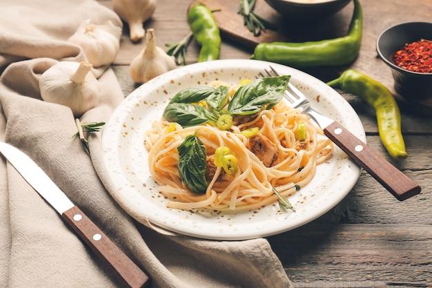 Prato com macarrão saboroso e frango na mesa de madeira