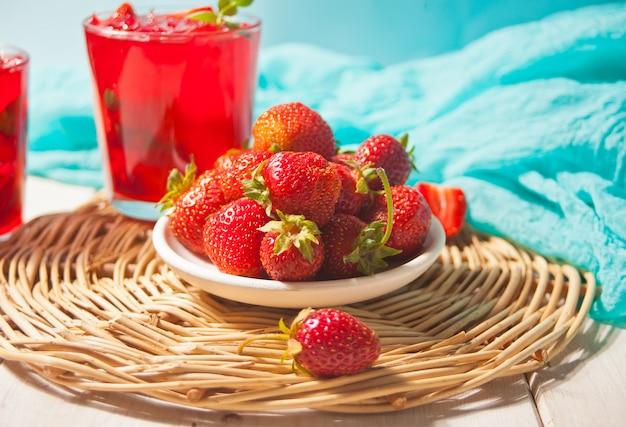 Prato com morangos frescos e copos com chá gelado doce de morango caseiro fresco ou coquetel, limonada com folhas de hortelã. bebida refrescante e fria. festa de verão.