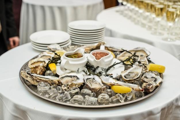 Prato com ostras vivas sobre a mesa no interior de um restaurante de luxo