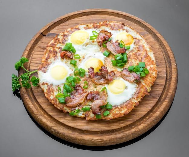 Prato com ovos fritos, bacon, tomate e bolos de chapa de batata close-up