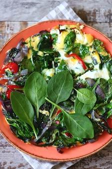 Prato com ovos mexidos com espinafre e legumes.