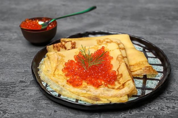 Prato com panquecas finas e caviar vermelho na mesa
