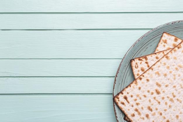 Prato com pão achatado judaico para a páscoa no fundo da mesa de madeira