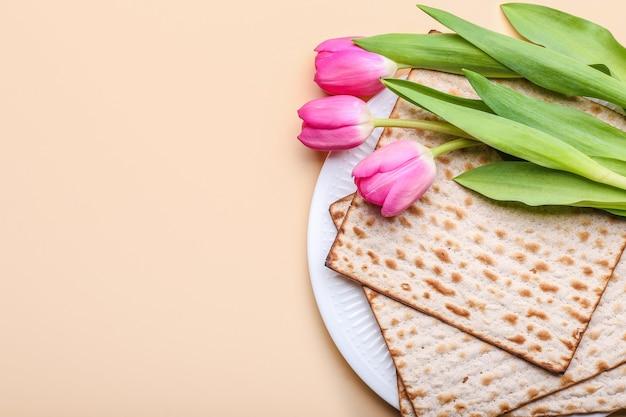 Prato com pão matza judeu para a páscoa e flores coloridas