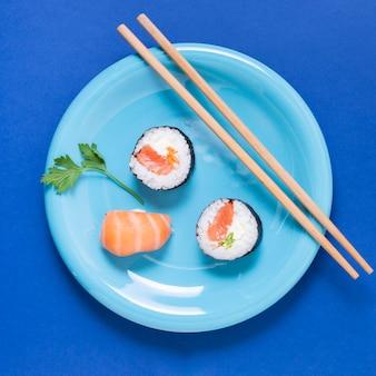 Prato com pauzinhos e rolos de sushi