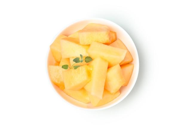 Prato com pedaços de melão isolados no fundo branco