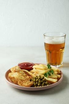 Prato com peixe frito com batatas fritas e cerveja isolada