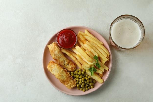 Prato com peixe frito e batatas fritas na mesa texturizada branca