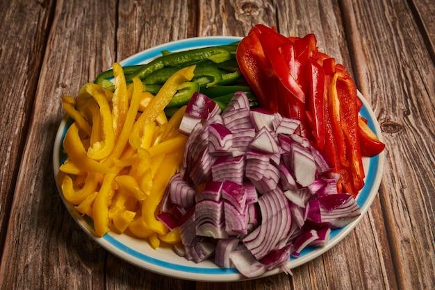 Prato com pimentões cortados coloridos verdes e amarelos vermelhos com cebola roxa em uma superfície de madeira