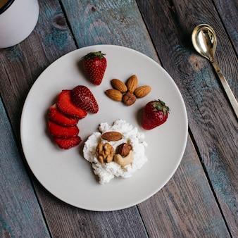 Prato com queijo cottage, morangos e nozes, uma xícara de café e toalhas na mesa de madeira, alimentação saudável, café da manhã