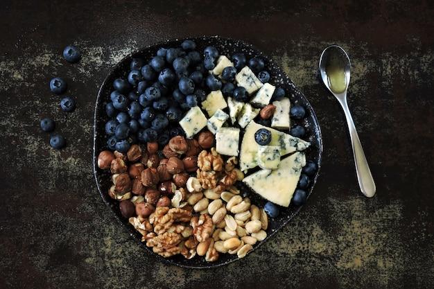 Prato com queijo, nozes e mirtilos.