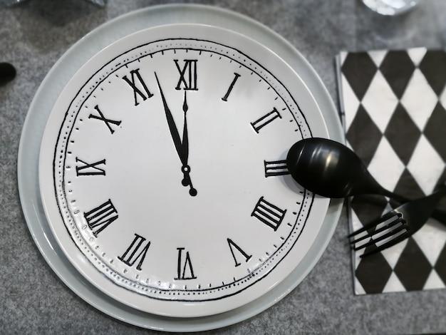 Prato com relógio, garfo preto e colher.