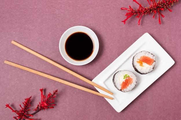Prato com rolos de sushi e molho de soja