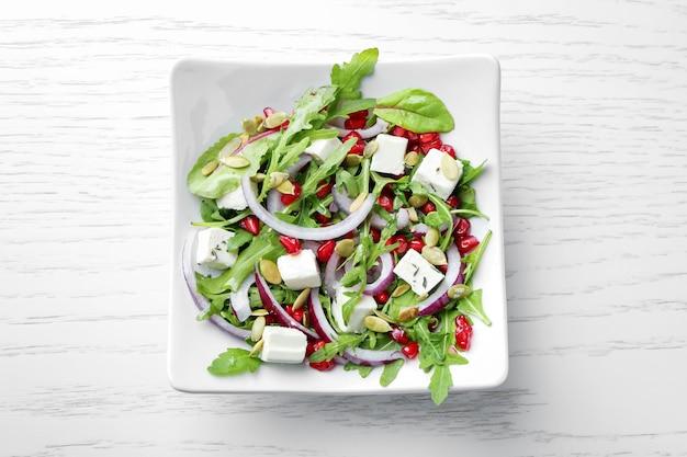 Prato com saborosa salada fresca na mesa de madeira