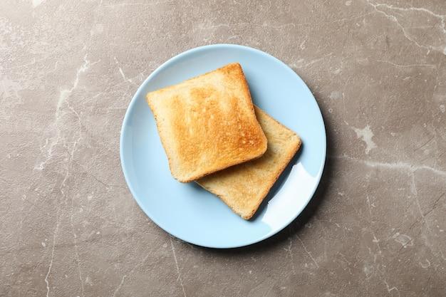 Prato com saborosas torradas no fundo cinza, vista superior
