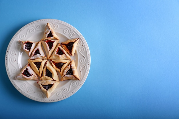 Prato com saboroso hamantaschen para o feriado de purim na cor de fundo