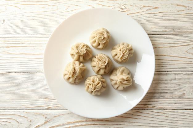 Prato com saboroso khinkali na mesa de madeira