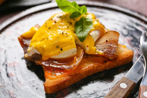 Prato com saboroso ovo benedict na mesa, closeup