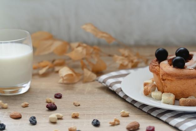 Prato com saboroso pão de canela assado com uvas pretas por cima, um copo de leite e muitas castanhas com passas na mesa de madeira