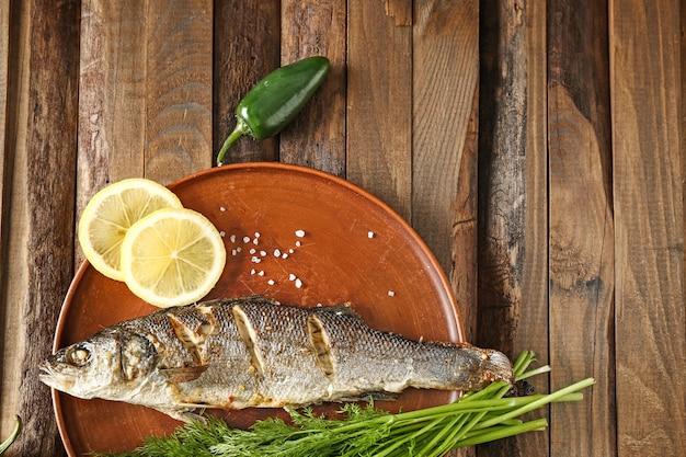 Prato com saboroso peixe cozido na mesa de madeira